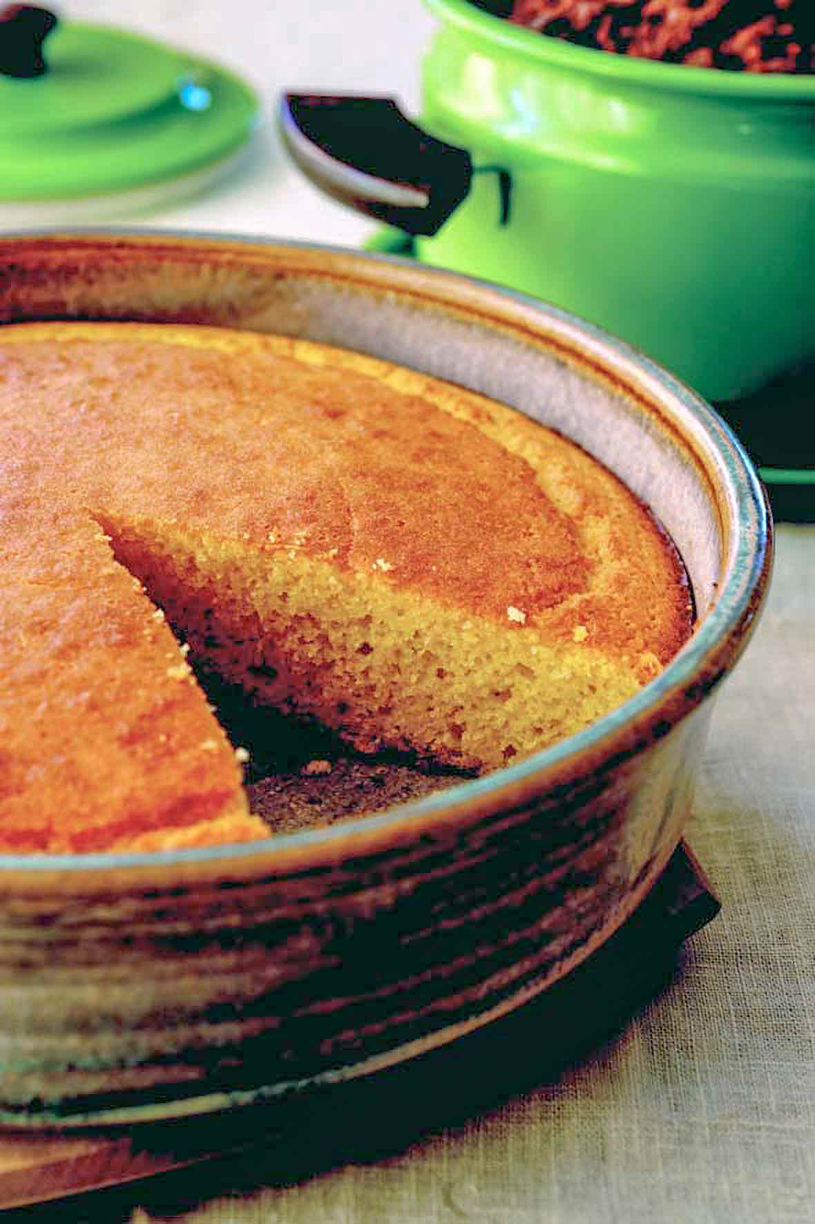 A cake pan of golden brown cornbread with a slice removed