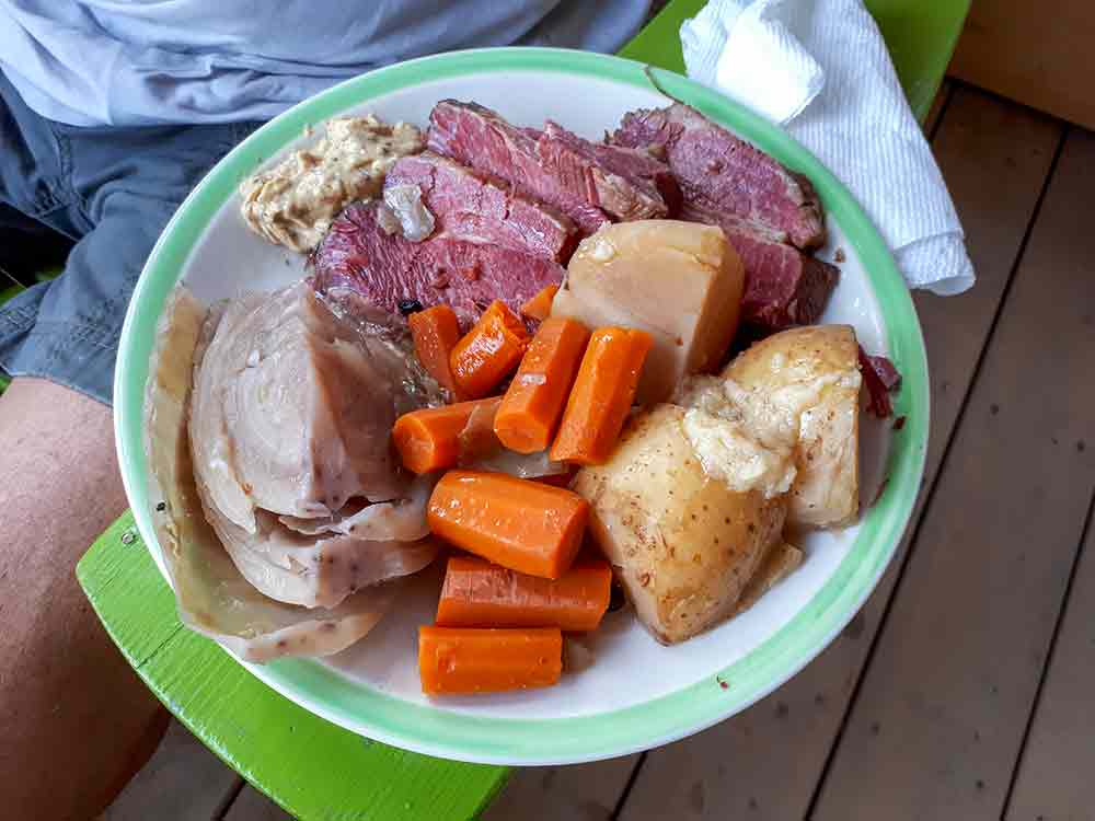 A plate of homemade corned beef with cabbage, potatoes, and carrots on the am of an outdoor chair
