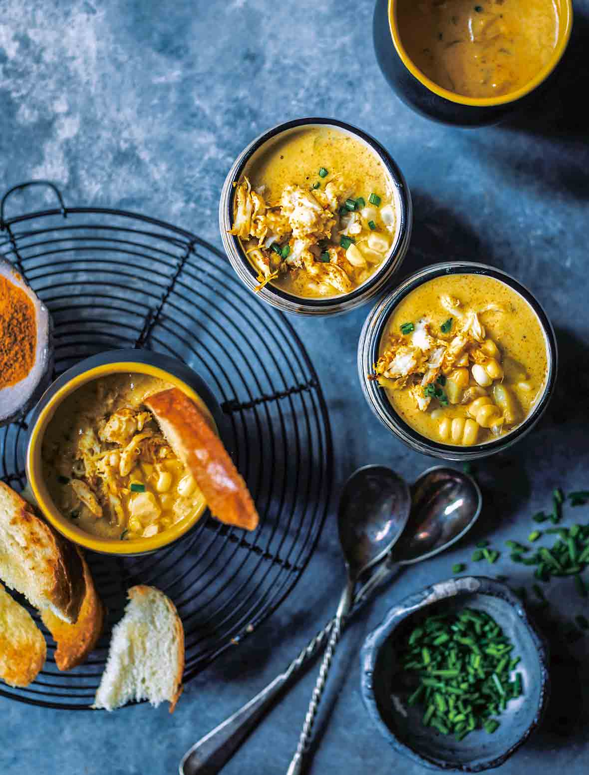 Four bowls of curried crab corn chowder, filled with crab, corn, and a curried broth, on bread and spoons nearby