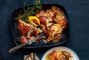 A black platter with golden brown herb butter chicken, roasted onion, a lemon wedge, and sprigs of thyme and oregano by Dorie Greenspan