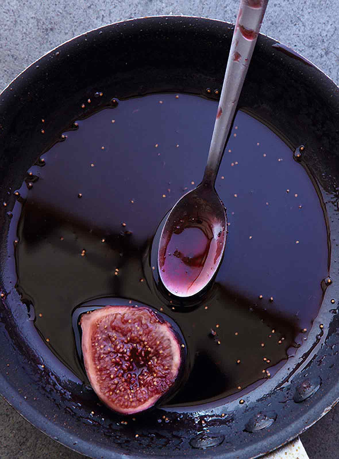 A black skillet with figs in Port wine and a spoon on the side