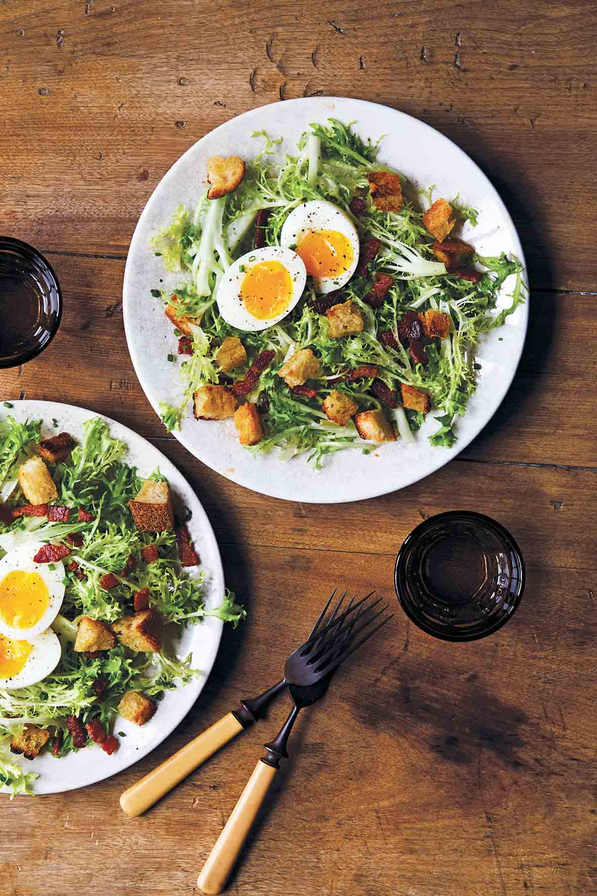 Two white plates of frisee salad with bacon and egg, croutons, and a dressing, glasses and fork and knife nearby