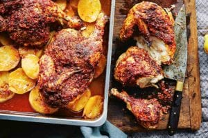 A pan of harissa roasted chicken sitting on top of sliced roasted potatoes, nearby a cutting board and knife