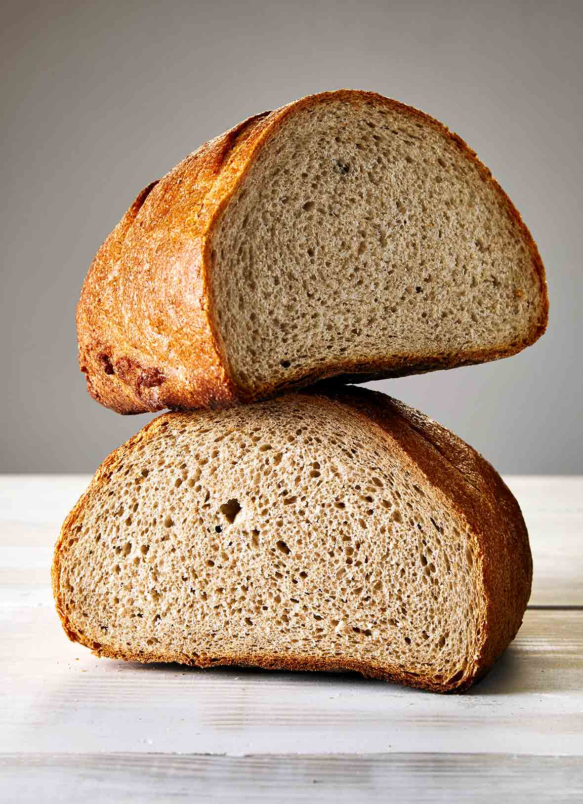 A loaf of Jewish rye bread, cur in half, one half balancing on the other