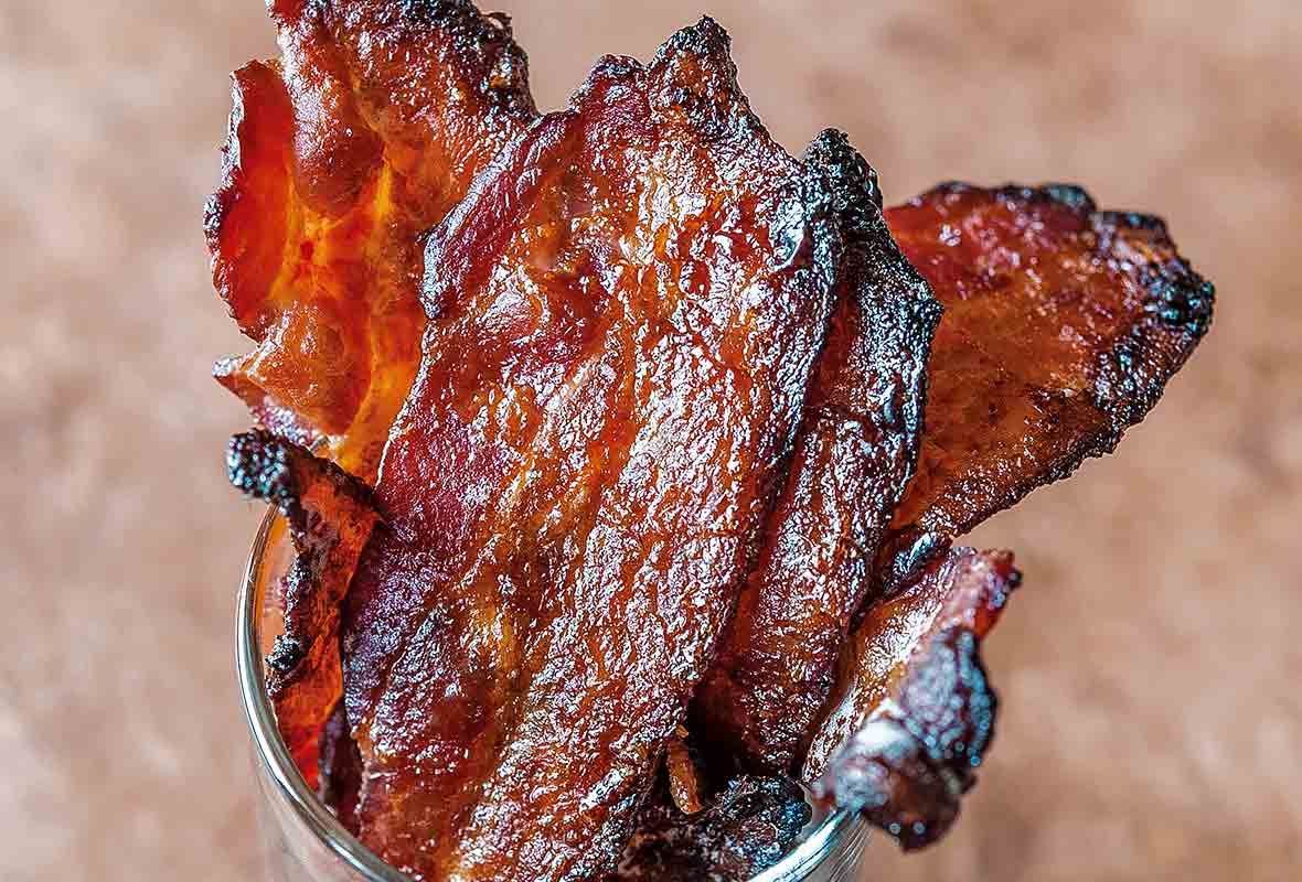 Cooked slices of maple sriracha bacon in a glass