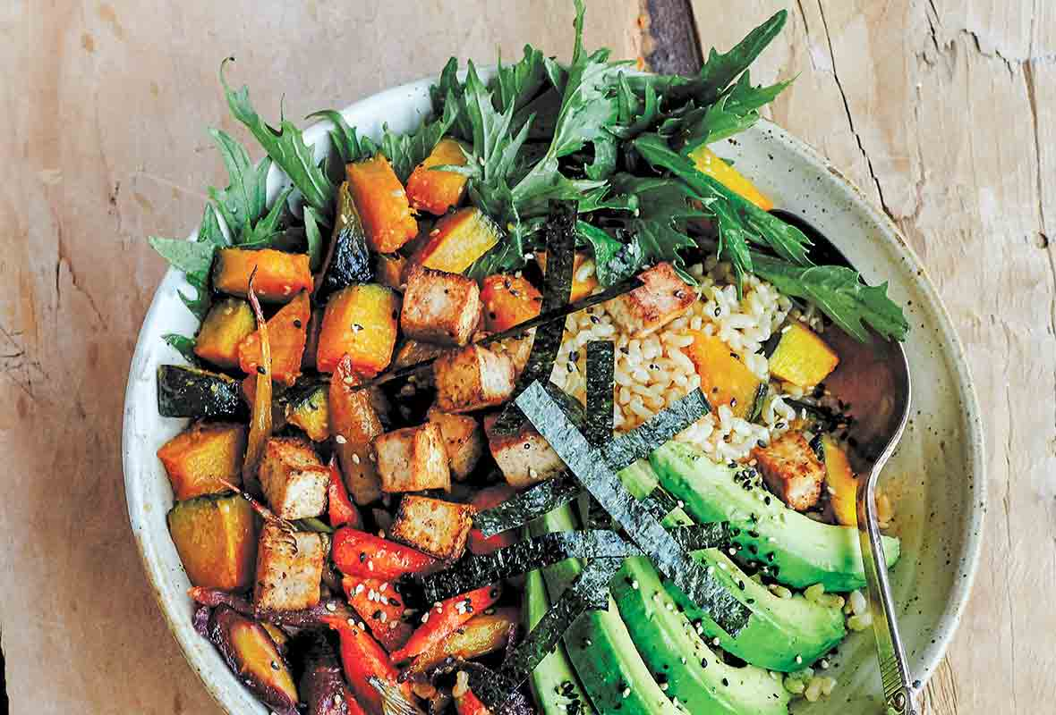 A bowl of miso-glazed kabocha squash with carrots, avocado, salad greens, seaweed over brown rice