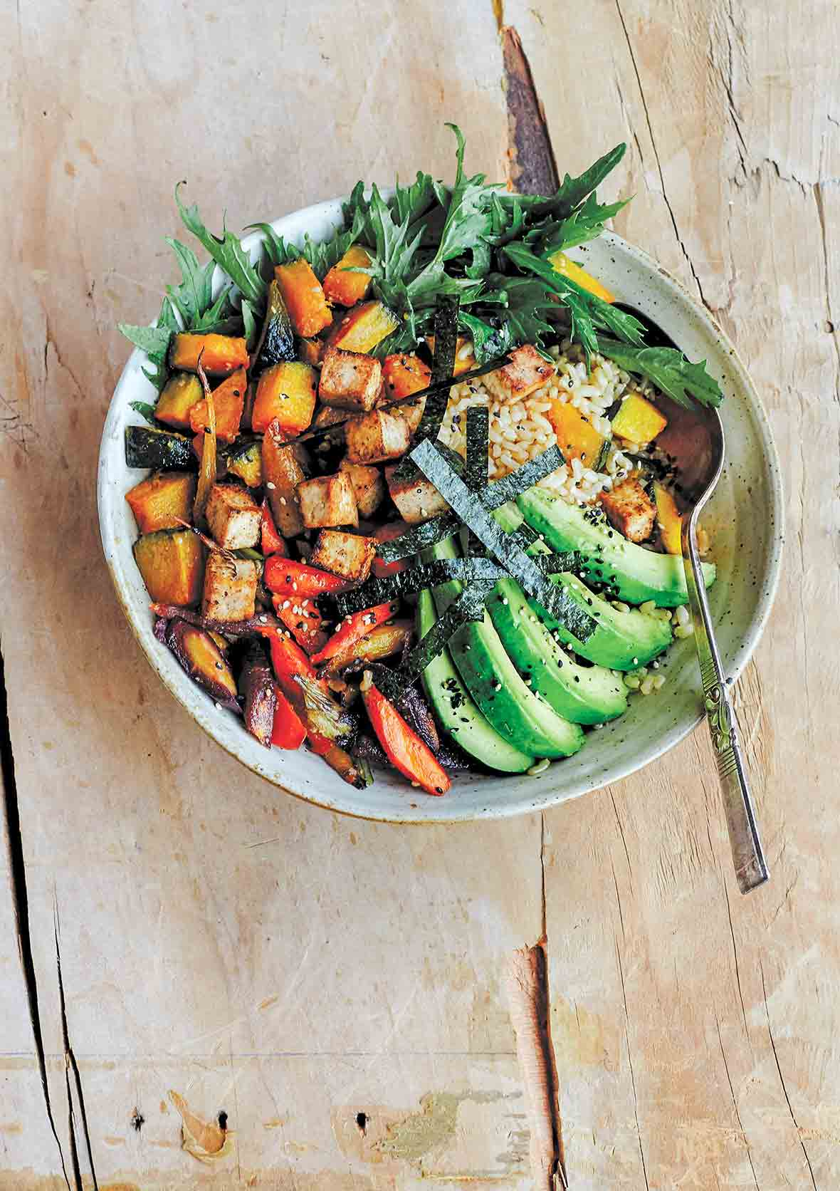 A bowl of miso-glazed kabocha squash with carrots, avocado, salad greens, seaweed over brown rice