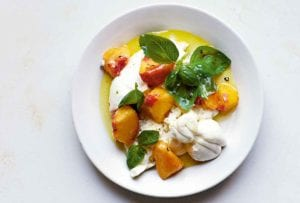 A white bowl filled with peach slices, chunks of burrata cheese, and basil leaves in a sweet syrup