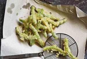 A pile of Portuguese peixinhos da horta (tempura green beans) draining on brown paper in a strainer, a spider spatula nearby