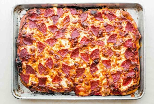 A sheet pan with pepperoni pan pizza, with cheese and pepperoni on top