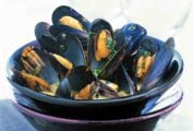 A bowl of pressure cooker mussels with saffron sprinkled with chopped parsley and in a yellow broth set in another bowl on top of a napkin
