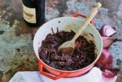 A red Le Creuset pot filled with red wine onions, that have been slowly cooked together