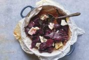 A pan lined with parchment paper containing sliced roasted beets, chunks of feta cheese, a dressing, and a spoon