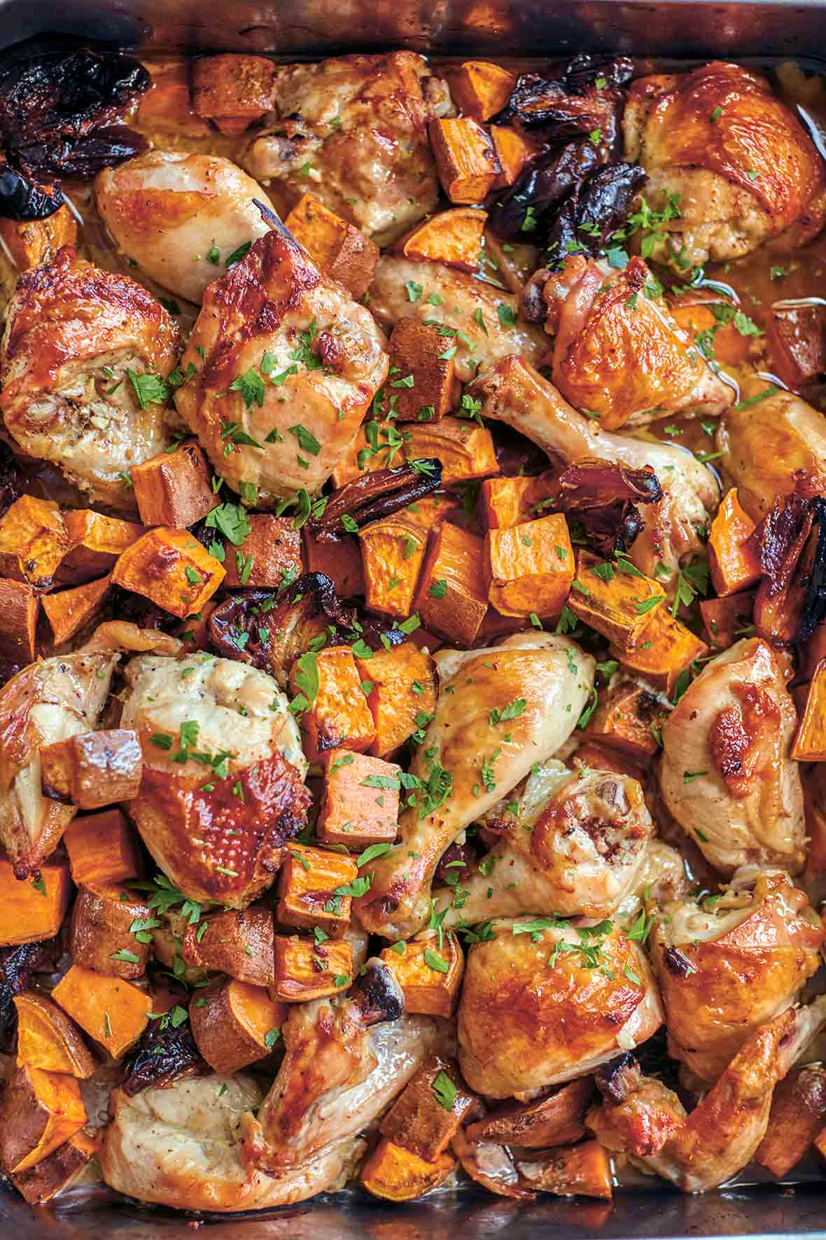 A sheet pan of Rosh Hashanah celebration chicken--roasted chicken pieces, sweet potatoes, onions, parsley