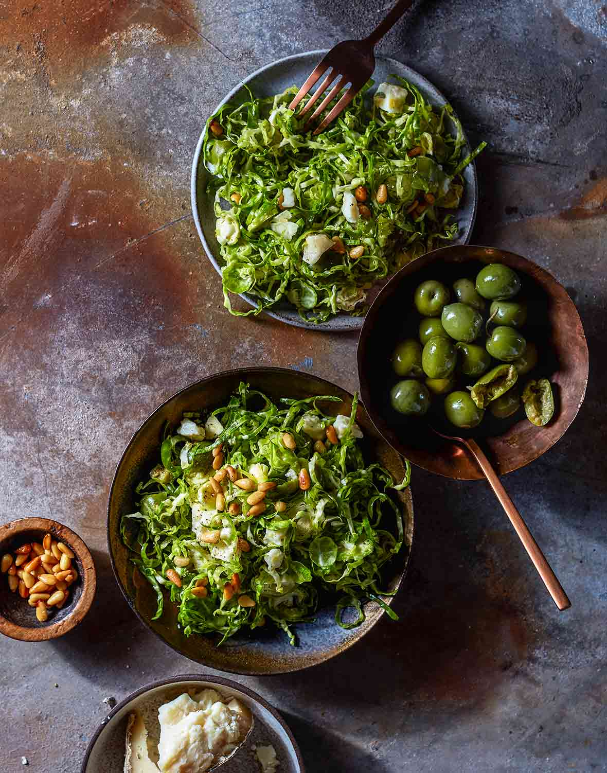 Two plates of shredded, shaved Brussel sprouts, topped with toasted pine nuts, green olives, bread, and more pine nuts nearby