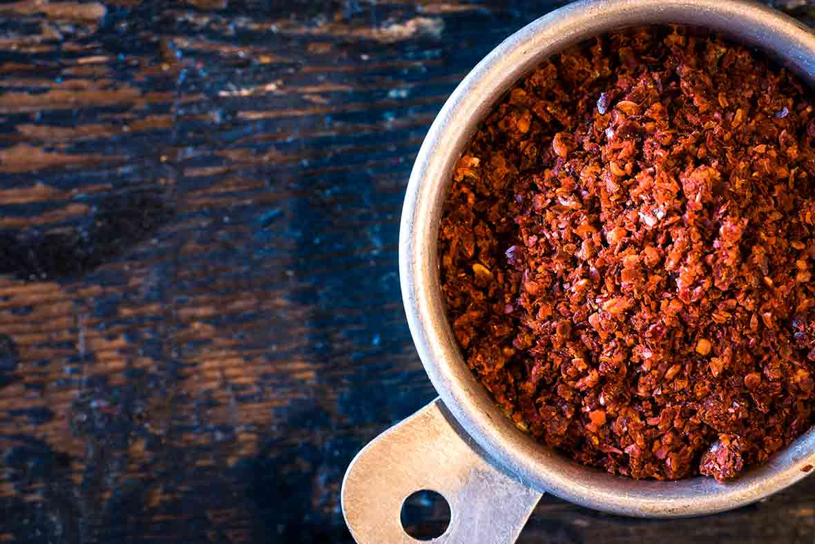 An antique measuring cup of aleppo pepper flakes