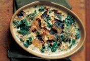 A ceramic oval dish of baked spinach mornay with cream sauce, sliced onion, and browned top