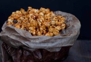 A waxed paper bag filled with caramel popcorn
