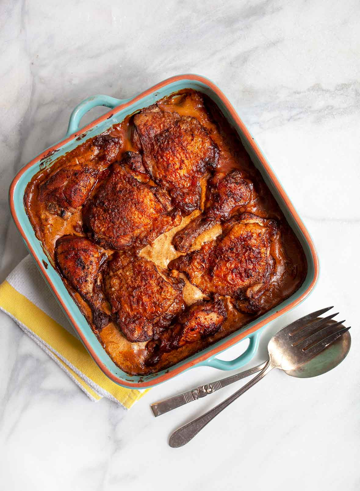 A blue earthenware dish with chicken paprikash--chicken thighs in a creamy paprika sauce, on a marble counter