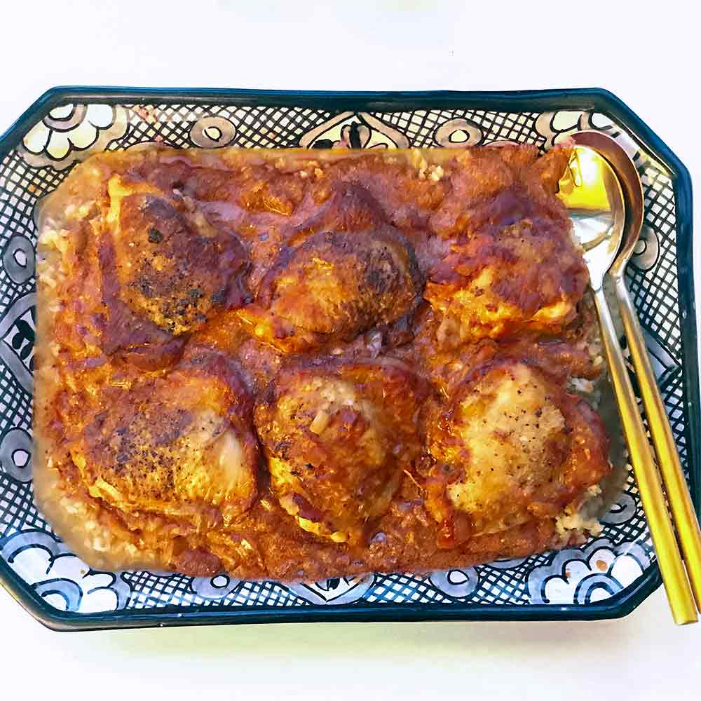 A blue and white plate with six thighs of chicken paprikash