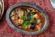 A metal serving dish of eggplant stew, called kawaj in Syria, filed with chunks of eggplants, potatoes, tomatoes with parsley on top