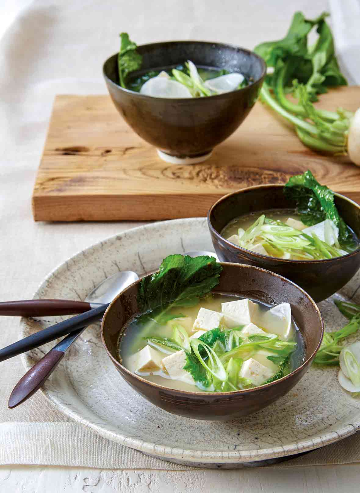 Two bowls of ginger miso soup with tofu, turnip greens, and miso broth