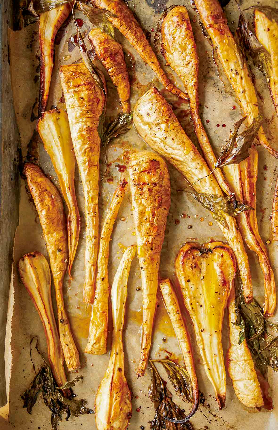 Sheet pan lined with parchment and sliced maple roasted parsnips