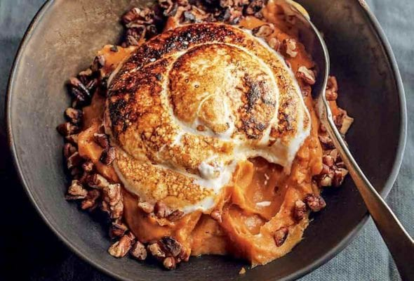 A bowl of sweet potato puree with marshmallow, which is toasted with a torch, toasted buttered pecans around the edge