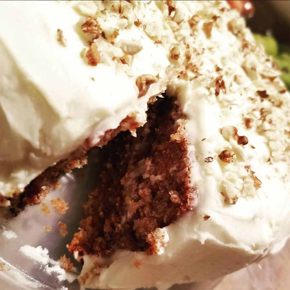 A carrot cake, with a slice removed, covered in cream cheese frosting and sprinkled with walnuts