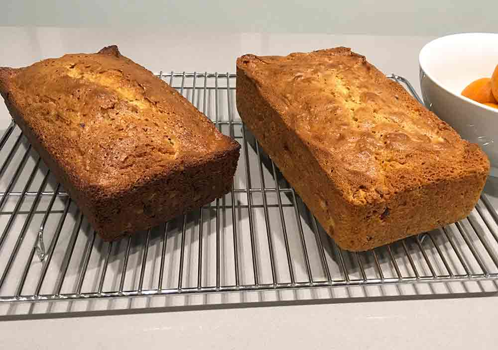Two loaves of cranberry orange pecan bread cooling on a wire rack