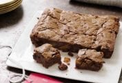 A square white platter with fruitcake brownies--filled with dried fruit, chocolate, and rum