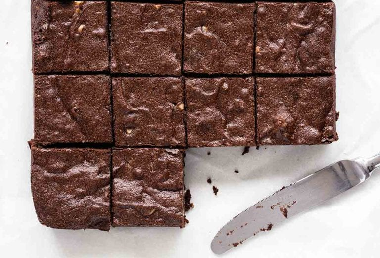 10 fat, chocolatey fudgy pudgy brownies sliced, with a table knife nearby with crumbs