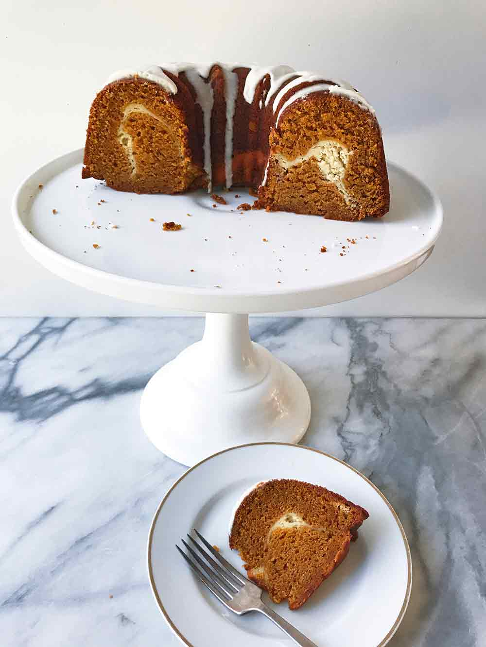 Half of a glazed pumpkin pound cake with a swirl of cream cheese filling inside on a cake stand, a piece on a plate nearby