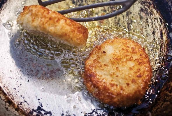 Old frying pan with two leftover mashed potato cakes being turned by a spatula