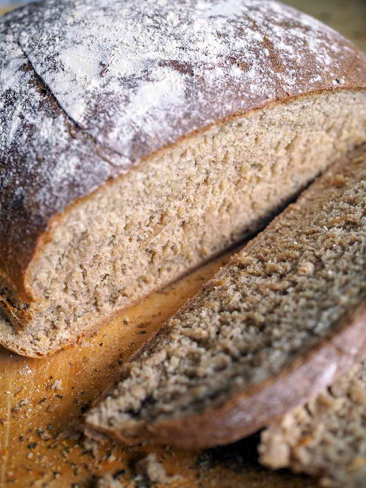A cut-open loaf of multigrain bread made with a mix of rye, barley, oats, whole wheat flours, and molasses, and milk