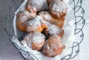 A wire basket of oliebollen or Dutch doughnuts covered with powdered sugar on a white tablecloth
