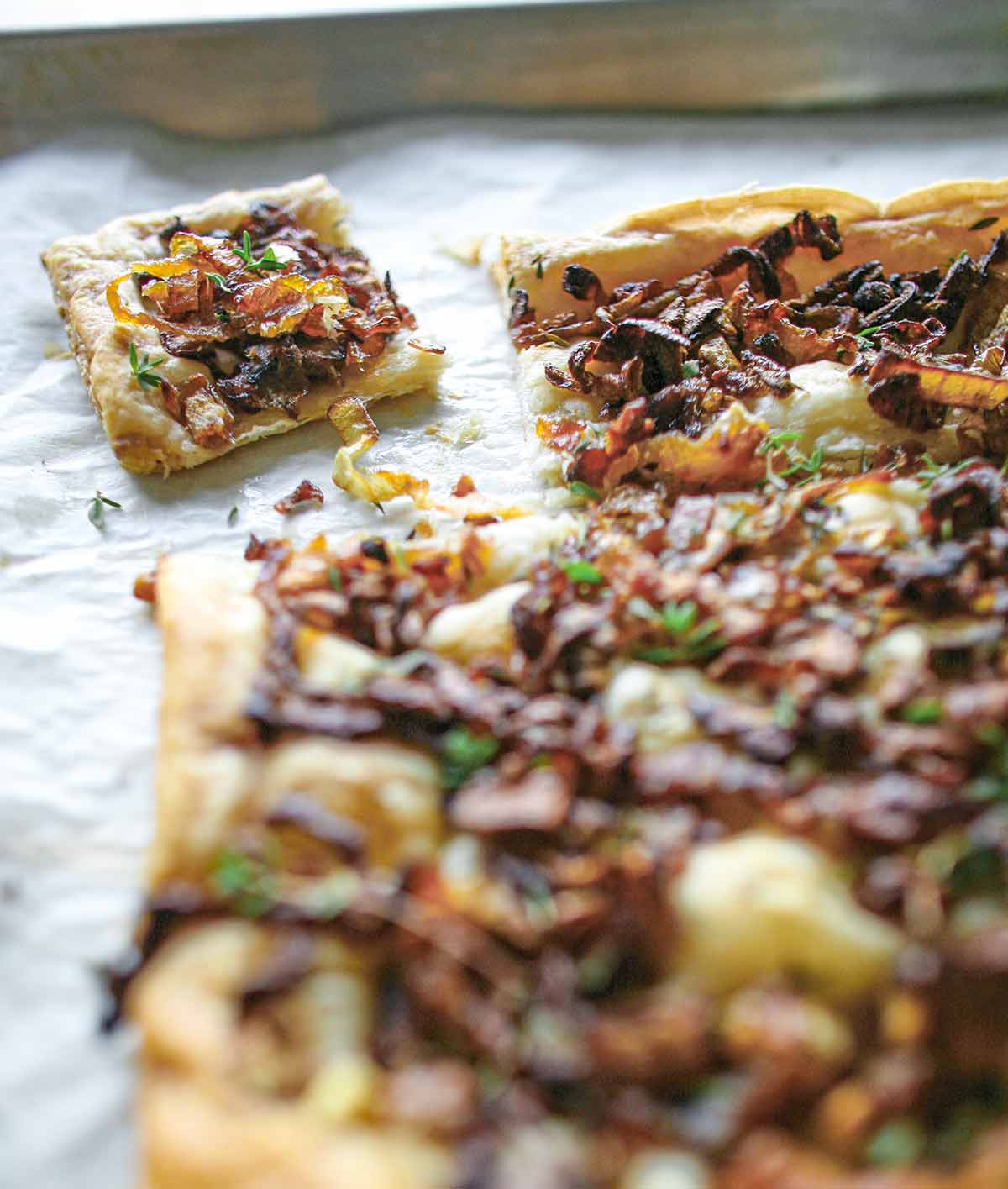 A sheet pan with an onion thyme tart on it, covered with cooked onions, thyme on a puff pastry crust