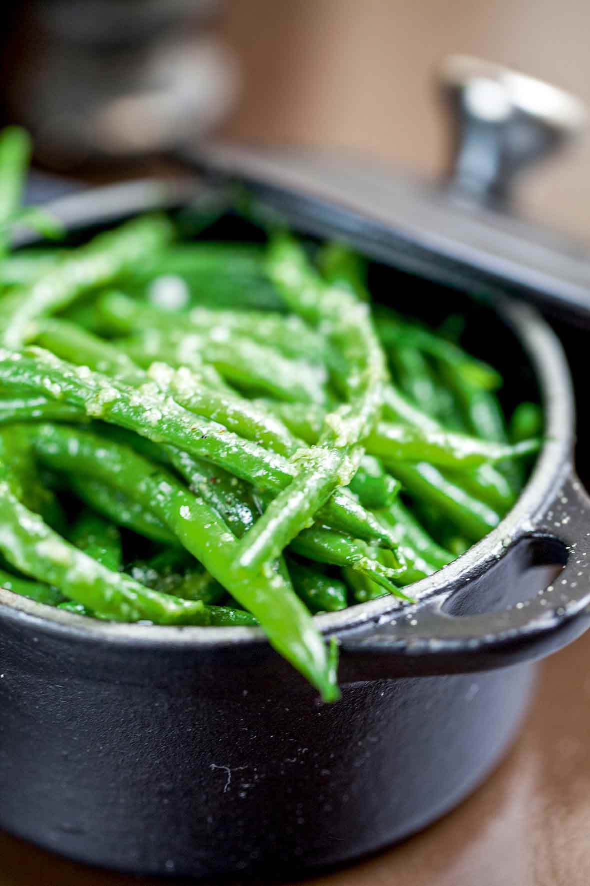 A cast-iron pot filled with pan-fried green beans tossed with garlic and butter