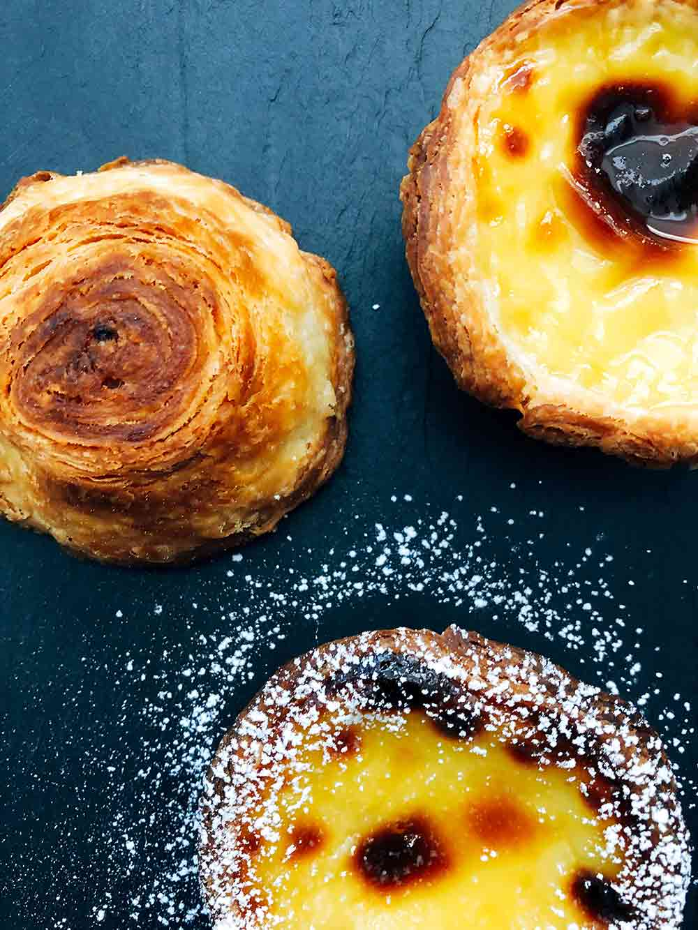 Three pasteis de nata, two face-up showing the browned spots and one upside-down, showing the delicate spiral of browned pastry