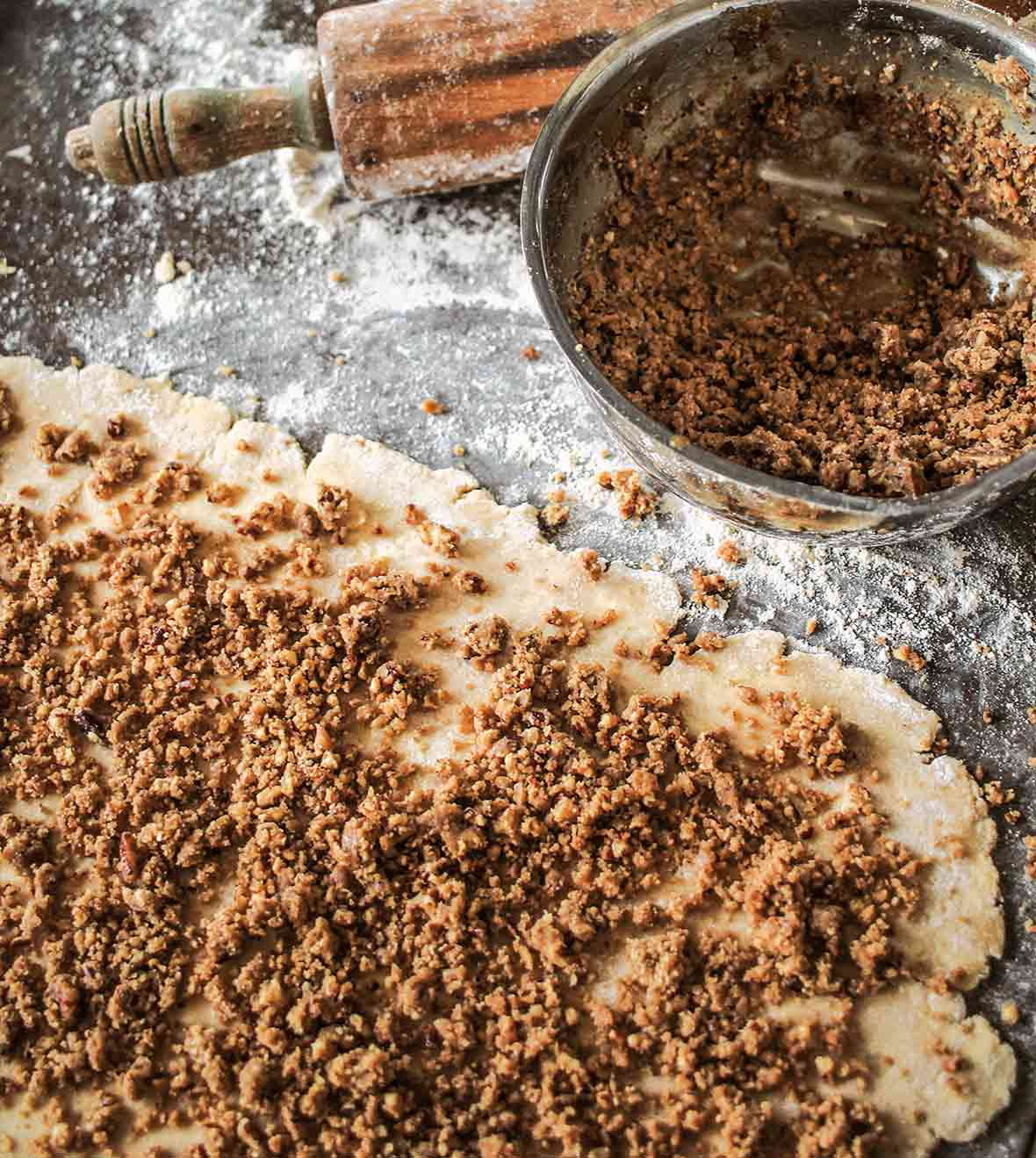 Rugelach dough covered with pecan pie filling and a bowl of filling nearby