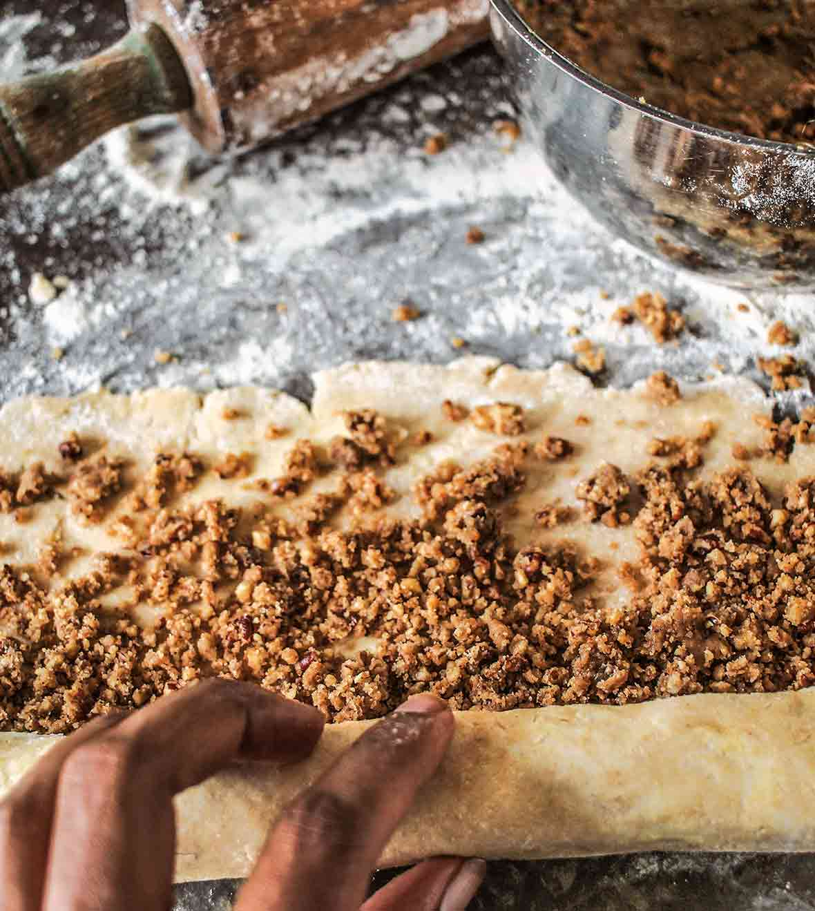 Rugelach dough covered with pecan pie filling being rolled up and a bowl of filling nearby