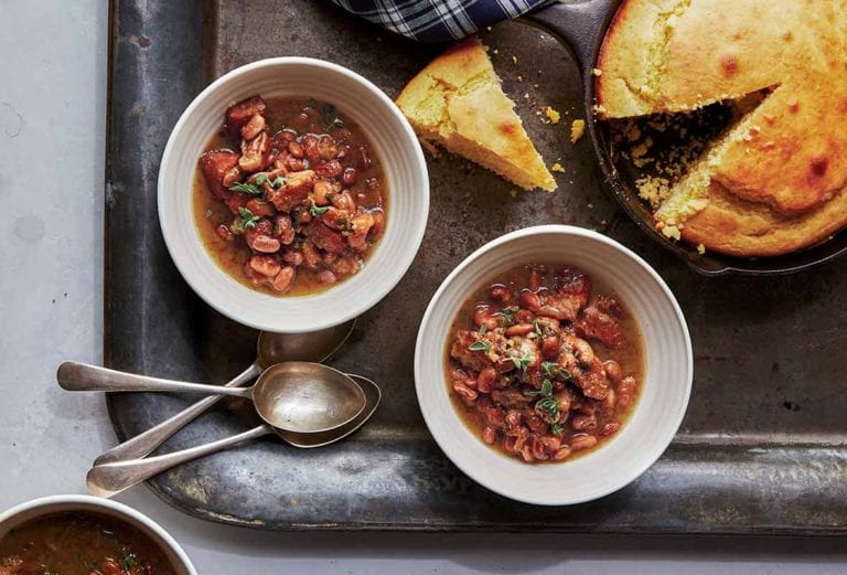 Three white bowls of pork and pinto beans chili on a metal tray with cornbread in a skillet