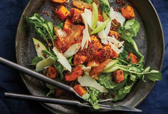 A pottery plate filled with roasted butternut squash and apple salad made with watercress, sweet apples, and topped with Parmesan