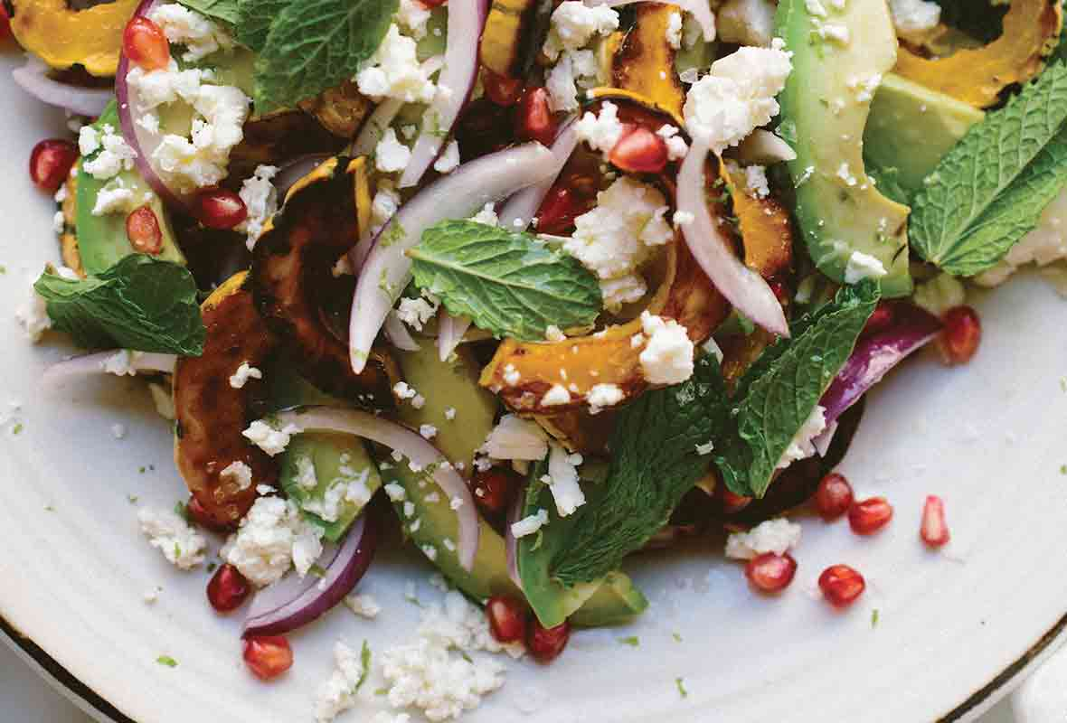 A plate of roasted delicata squash salad with red onion, feta cheese, avocado, and mint