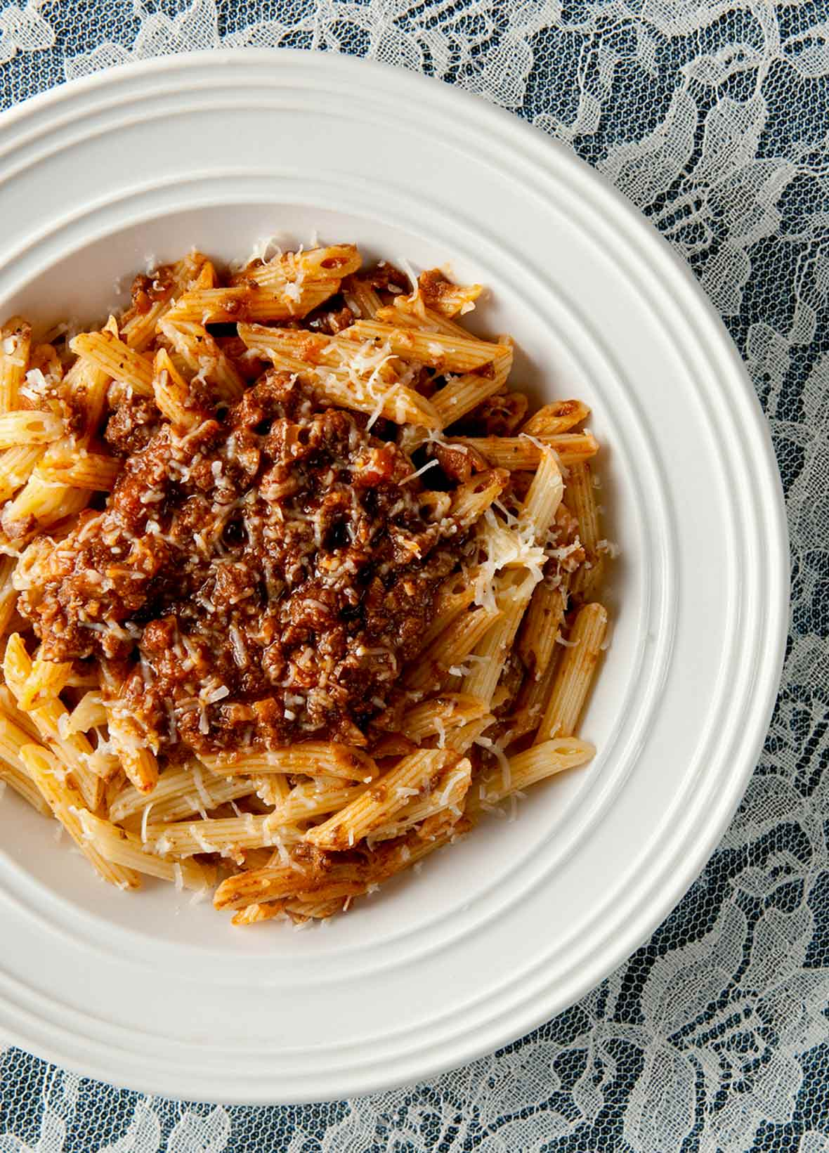 White bowl of venison Bolognese made with ground venison, carrots, onion, celery, mushrooms a top rigatoni