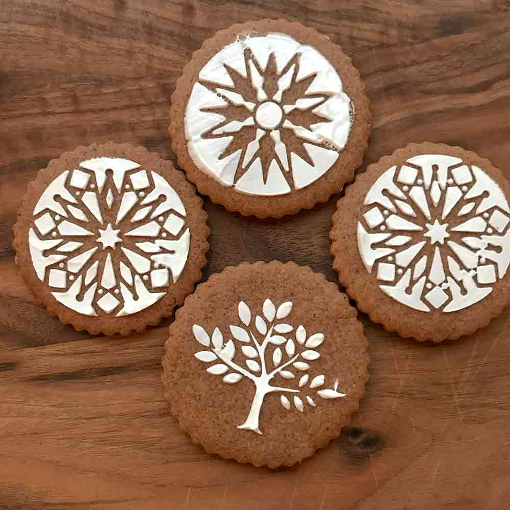 Four Swedish black pepper cookies called pepperkakor decorated with snowflake and tree icing designs