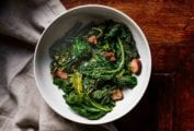 A bowl of braised greens--spinach, kale, collards--and chunks of andouille sausage