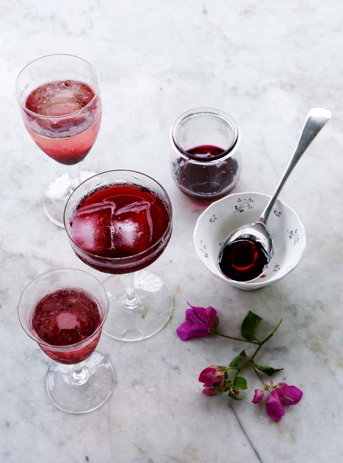 Several glass filled with purple Christmas hibiscus cocktail