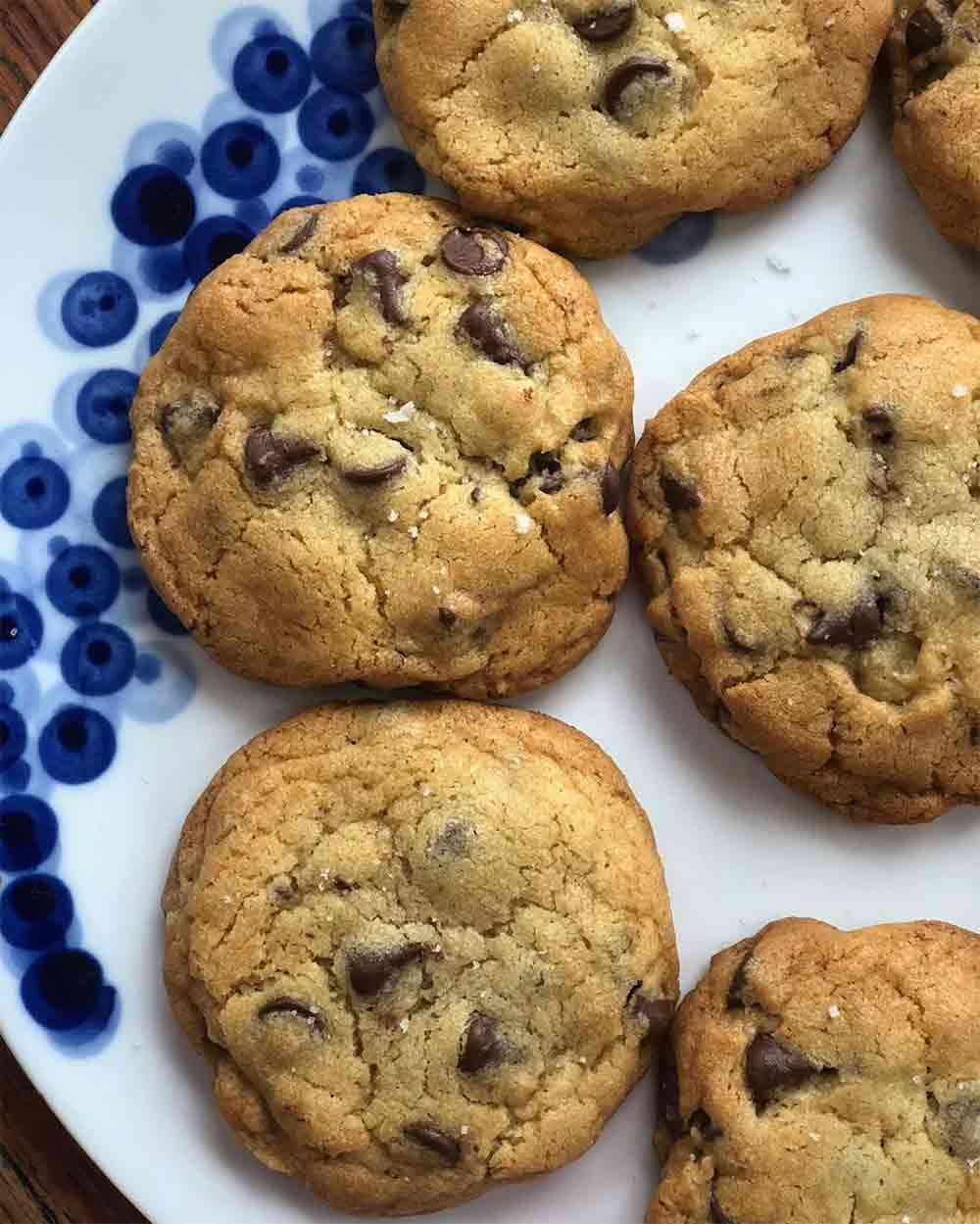 Six chocolate chip cookies on a blue and white plate