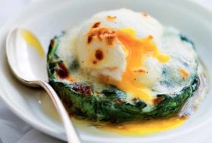A white bowl with a easy eggs Florentine--a poached egg on top of a bed of cooked spinach